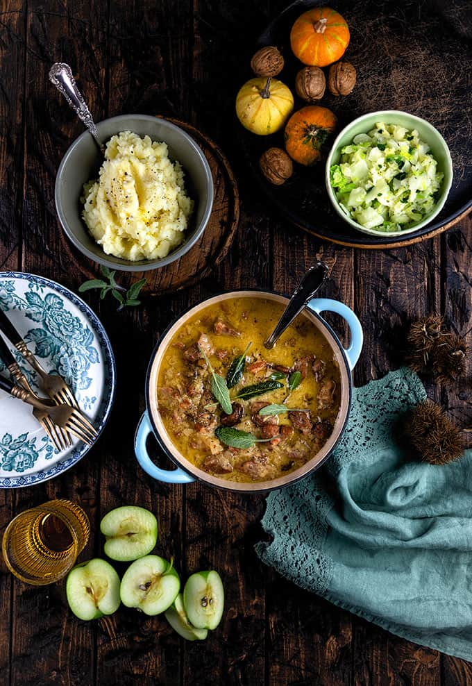 French pork casserole with cider and apples in a cast iron pot