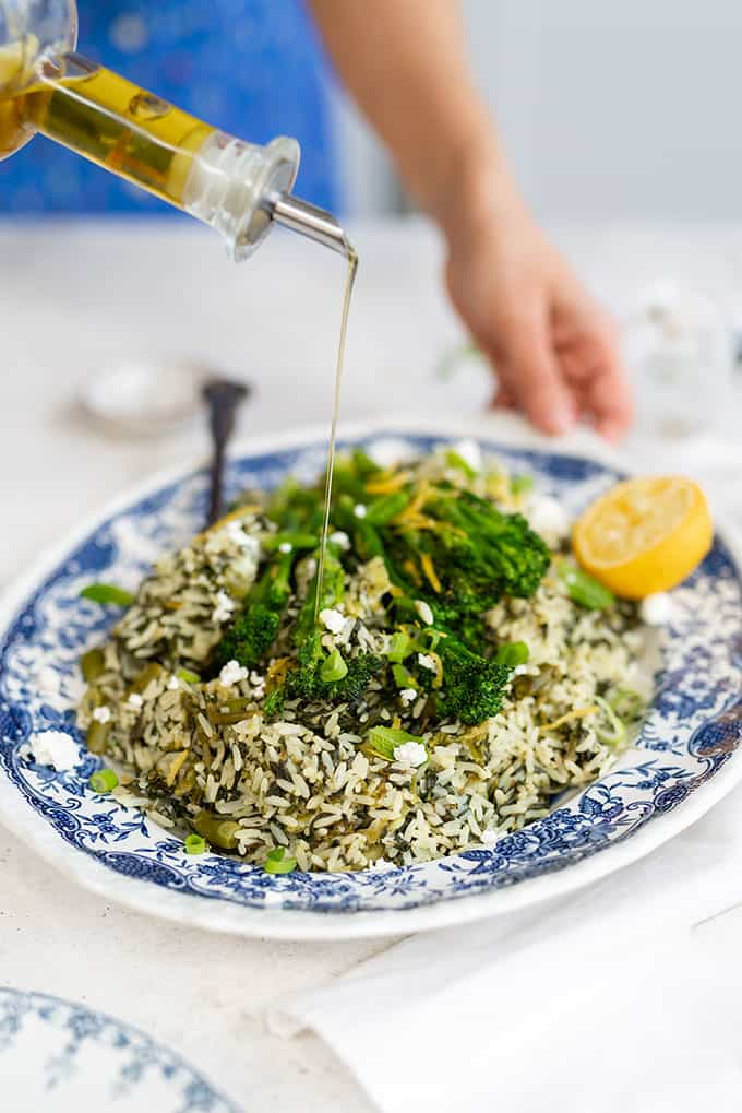 Platter of Greek spinach rice topped with broccoli spears with olive oil drizzle