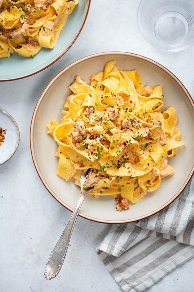 Creamy salmon chorizo pasta in a bowl garnished with chives