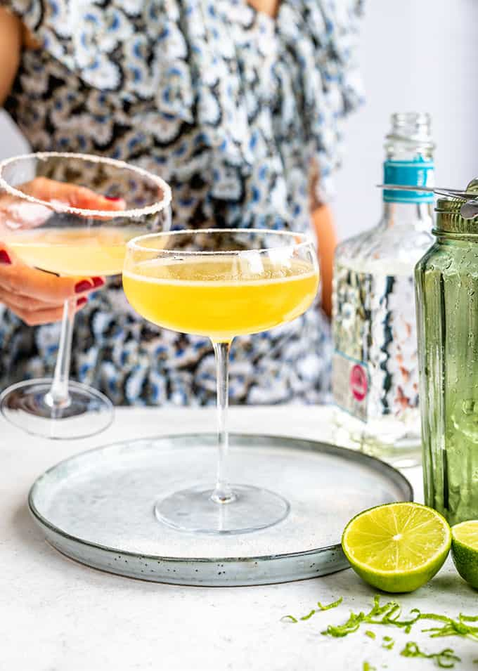 Cadillac Margaritas in a coupe glass with person in background