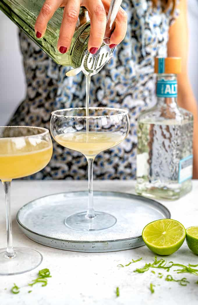 Straining a Cadillac Margarita into a coupe glass frosted with salt