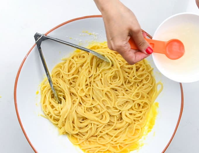 Adding reserved pasta water to bowl of spaghetti carbonara to make sauce creamier