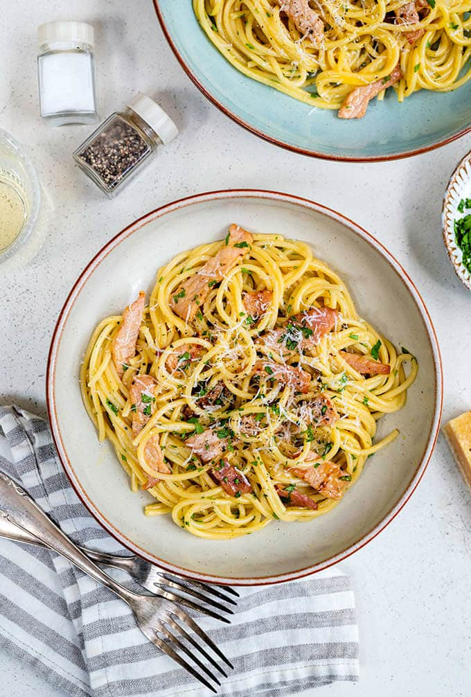 Overhead shot of spaghetti carbonara served in a shallow pasta bowl garnished with grated parmesan and chopped parsley