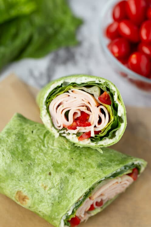 close up tortilla with turkey, lettuce, and tomato