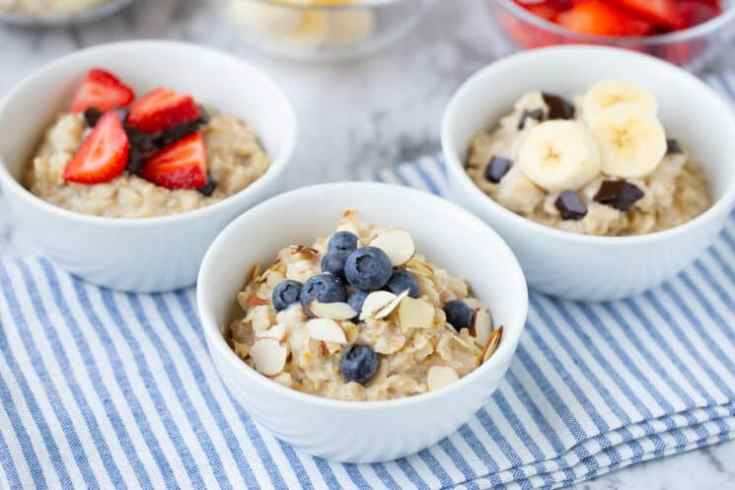 white bowls of oatmeal on a blue and white striped tablecloth are filled with an assortment of fresh toppings