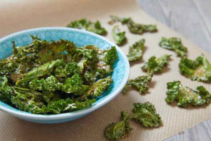 crispy kale chips in a blue bowl on a wooden table