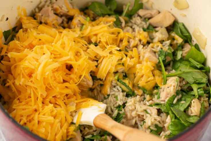 grated cheese, rice, and spinach in a pot being stirred up