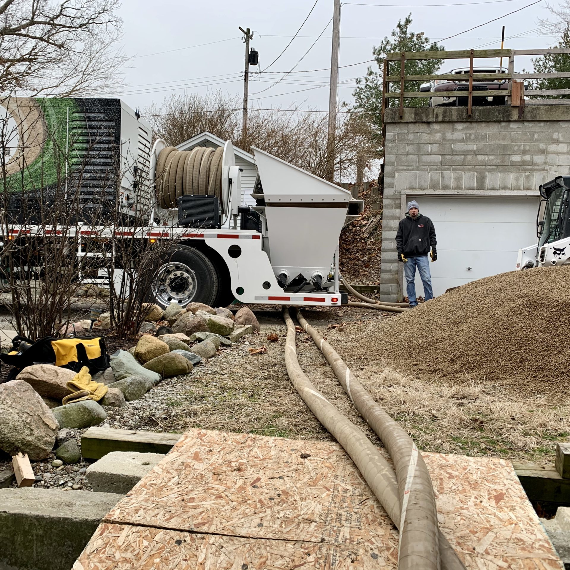 Superior Groundcover stone blower truck installing peastone under a house