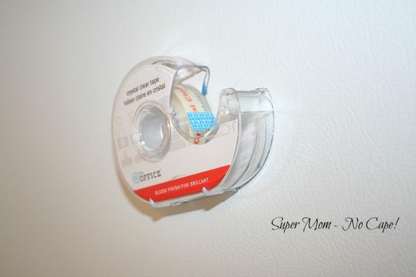 Tape dispenser hanging on side of fridge.