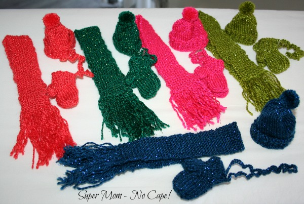 Photo of five miniature hats, mittens and scarves