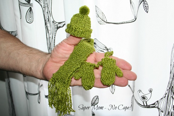 Photo of hand holding green hat, scarf and mittens.
