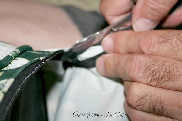 Cut away 4 or 5 of the zipper teeth