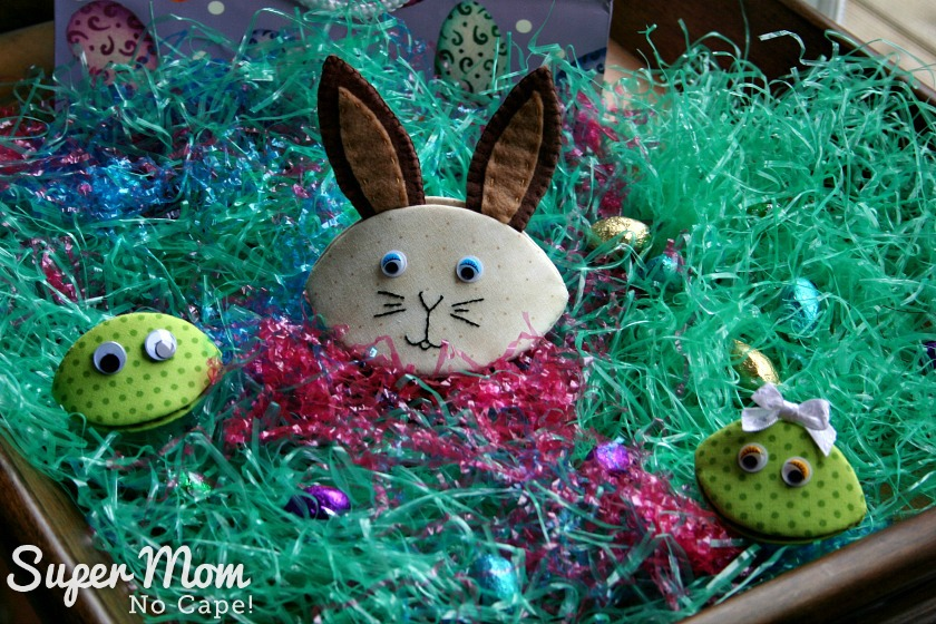 Photo of Bennet Bunny, Frankie and Frannie Frog on a bed of Easter Grass with foil wrapped chocolate eggs scattered around