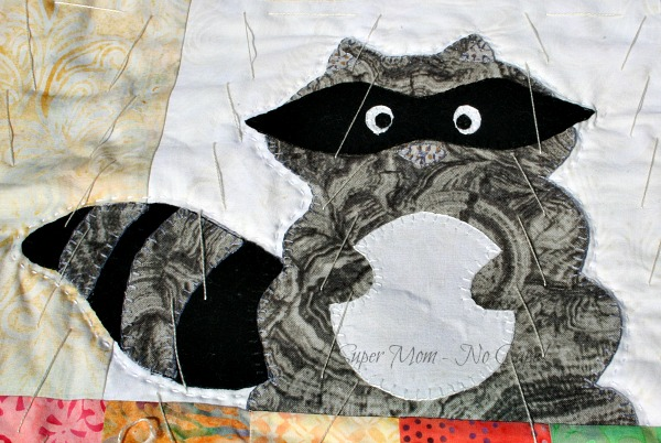 Hand quilting done around the appliqued raccoon.