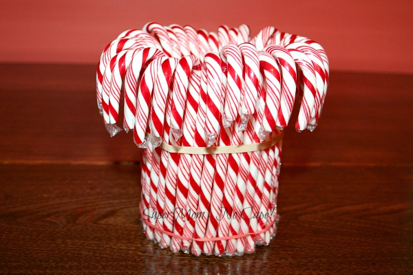 Insert Candy canes between rubber band and vase