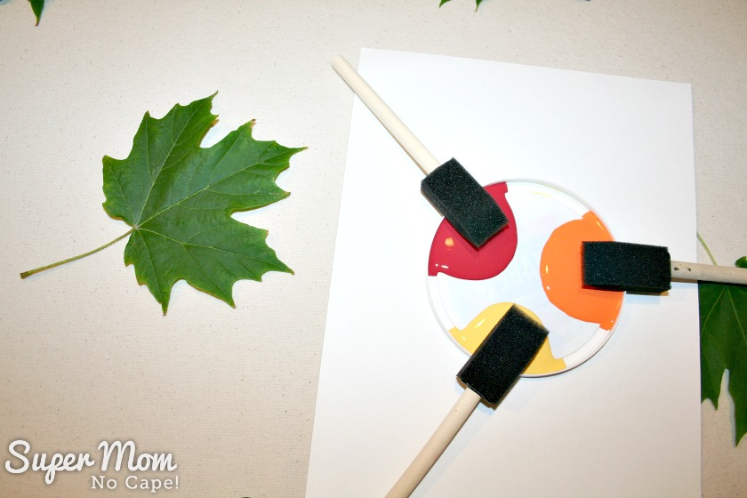 Paint tray with three color of paint and sponge brushes ready to paint a leaf on the Painted Maple Leaf Table Runner