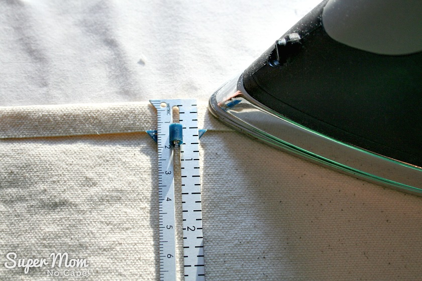 Pressing under one half inch along one long side of the canvas for the Maple Leaf Table Runner to get it ready to hem