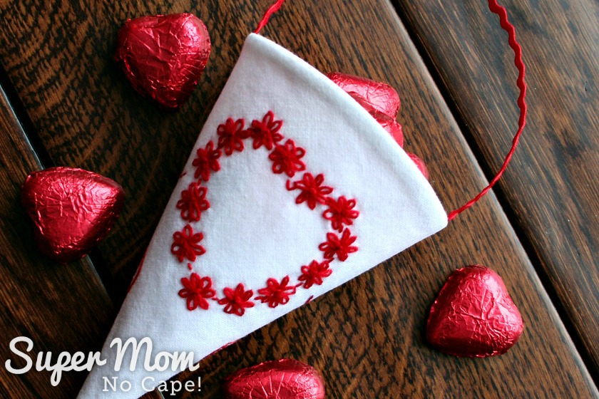White Fabric Treat Cone with Red Floral Embroidered Heart filled with candy laying on a wooden table