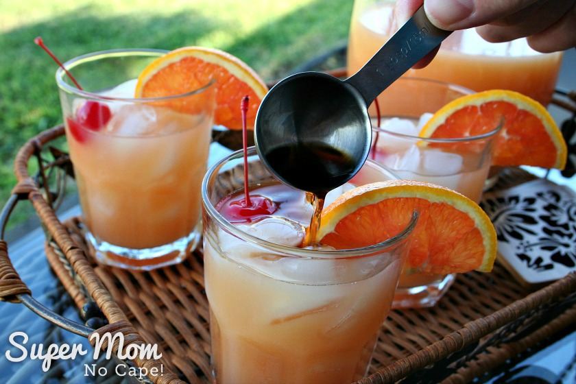One tablespoon of dark run being added to a glass with the Mai Tai mix