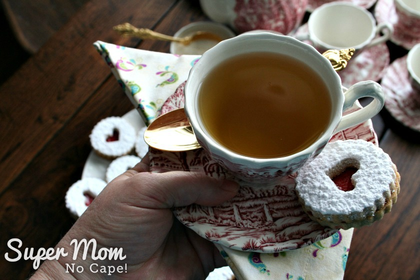 Cup of Herbal Tea on a Saucer with a Snow Storm Linzer Cookie and gold teaspoon