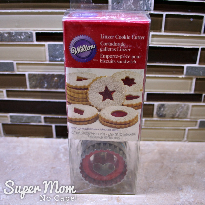 Photo of a Wilton Linzer Cookie Cutter Kit sitting on a kitchen counter with the brown tiles backsplash in the background