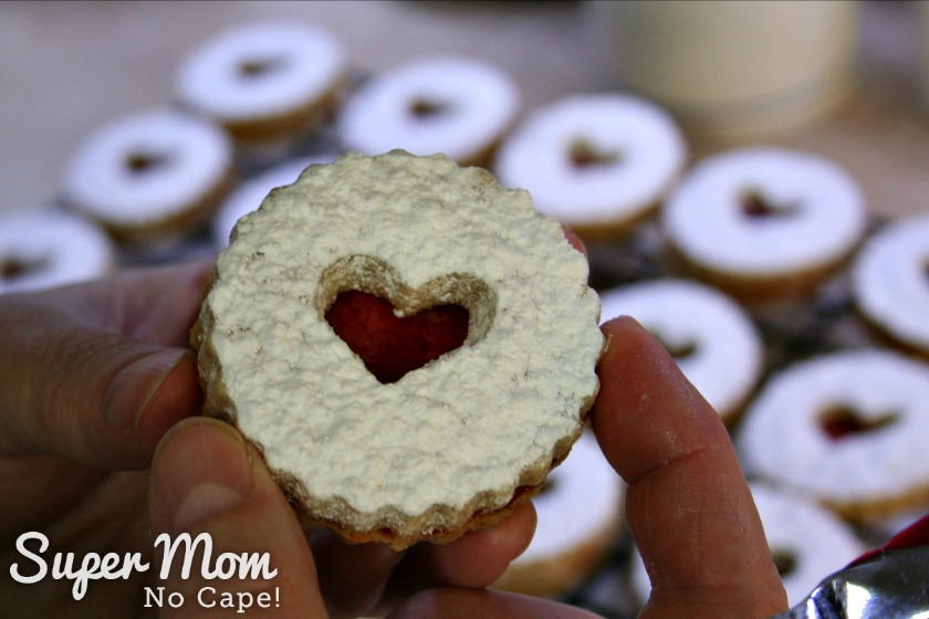 Photo of the icing sugar dusted top being placed on the raspberry spread bottom of the Snow Storm Linzer cookie