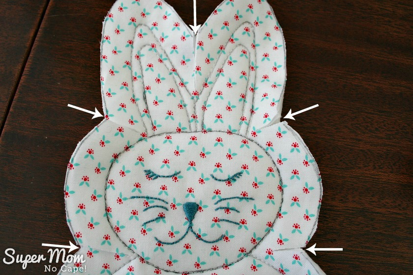 Close up of bunny head with white arrows showing where to clip