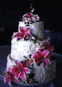 Picture of a White wedding cake, three-tier, with star gazer lilies