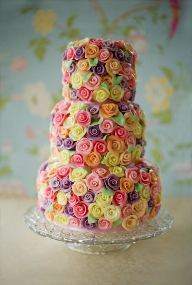 Multicolored wedding cake with roses.