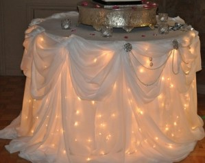 round wedding cake table with twinkle lights