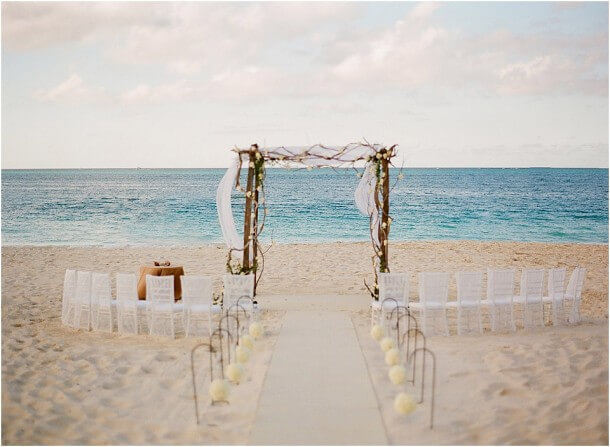 Decor for beach wedding ceremony with rustic canopy