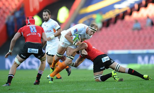 Warren Whiteley and Franco Mostert of Lions tackle Carl Wegner