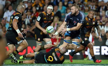 Bulls' RG Snyman (C) passes the ball in the tackle of Chiefs Tawera Kerr-Barlow during the super rugby match between the Waikato Chiefs and Northern Bulls at FMG Stadium in Hamilton