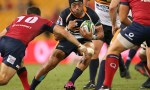 Christian Lealiifano is tackled during round two of the Super Rugby match between the Reds and the Brumbies