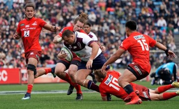 JP Smith of Reds is tackled during the Super Rugby match between Sunwolves and Reds at Prince Chichibu Memorial Ground