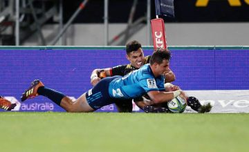 Harry Plummer of the Blues scores a try against Shaun Stevenson of the Chiefs during the round 14 Super Rugby match between the Blues and the Chiefs at Eden Park