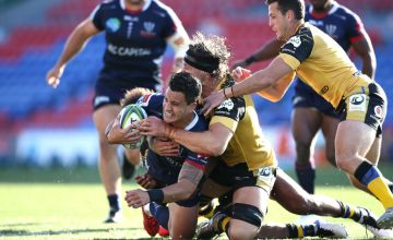 Matt To'omua of the Rebels is tackled during the round 10 Super Rugby AU match between the Melbourne Rebels and the Western Force at McDonald Jones Stadium