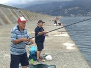 Pescatori sulla diga del porto di Pra'