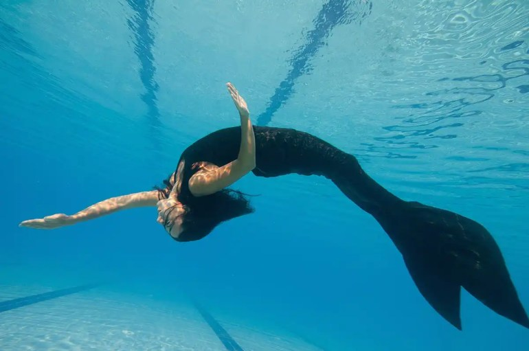 woman with mermaid fin in pool