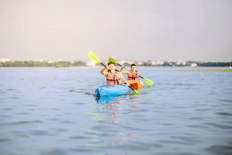 men kayaking on lake