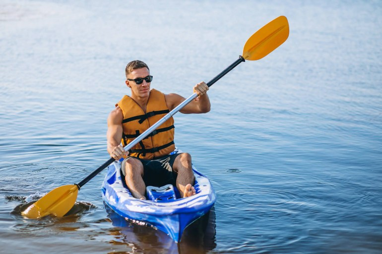 man with life vest on kayak