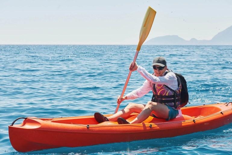 man kayaking on sunny day