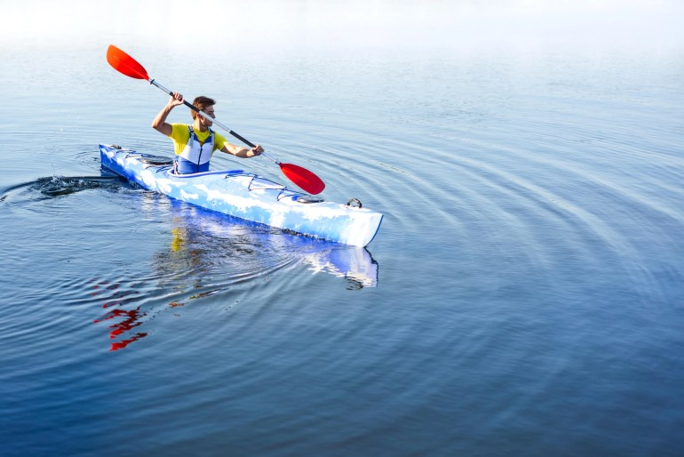 young man in blue kayak