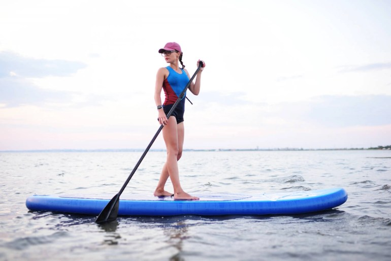 girl standing on an inflatable paddle board