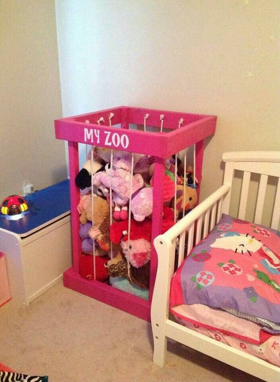 """Pink wooden box with vertical rope """"bars"""" used for storing stuffed animals."""