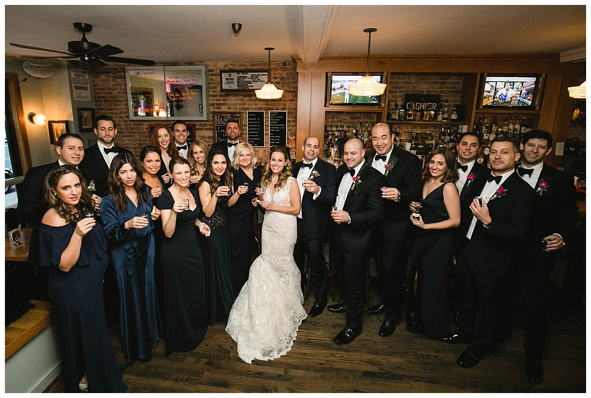 A bride and a groom with their wedding parties hanging out in a bar on a wedding day at Guastavinos in New York City. Dress by Ines Di Santo.
