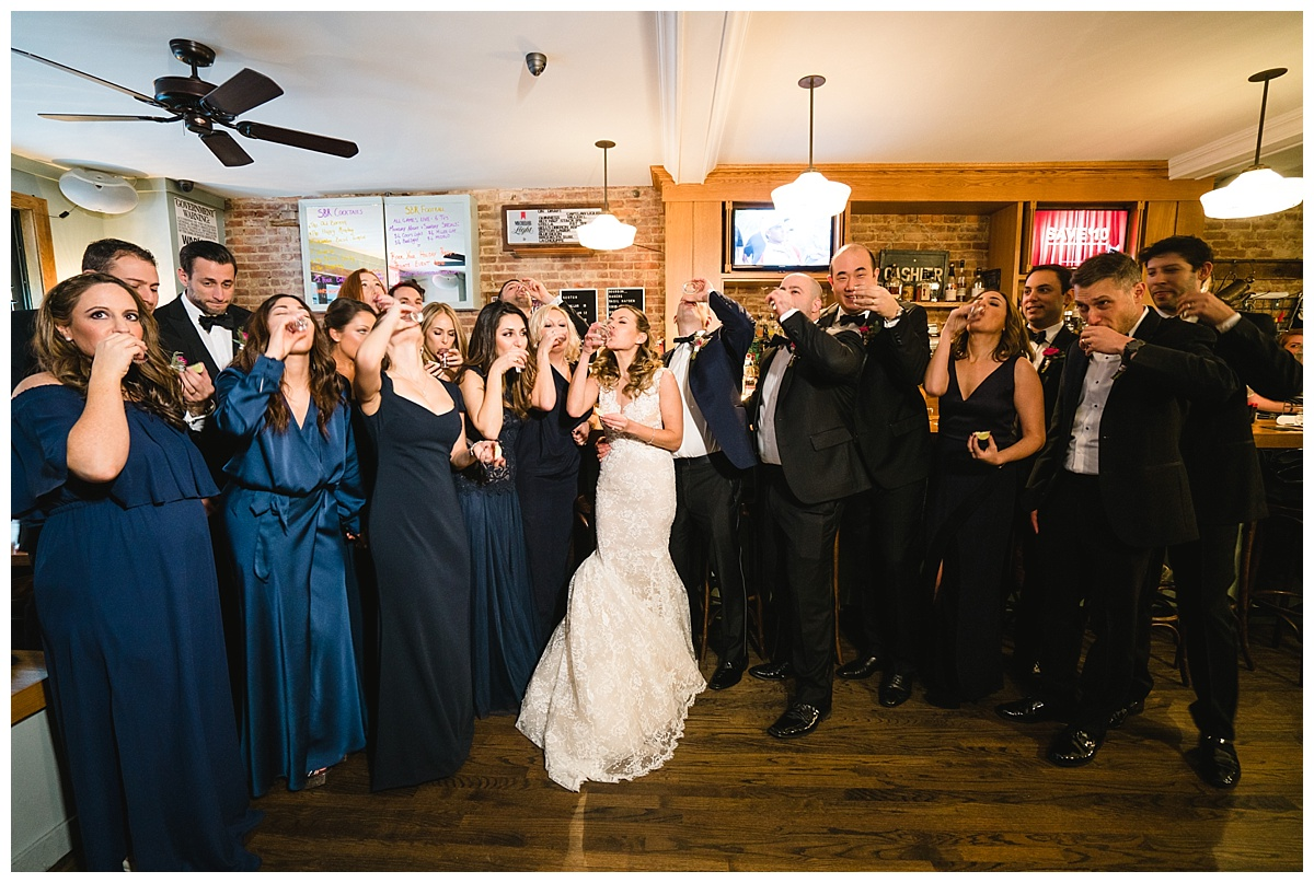 A bride and a groom drinking a shot with their wedding parties and hanging out in a bar on a wedding day at Guastavinos in New York City. Dress by Ines Di Santo.
