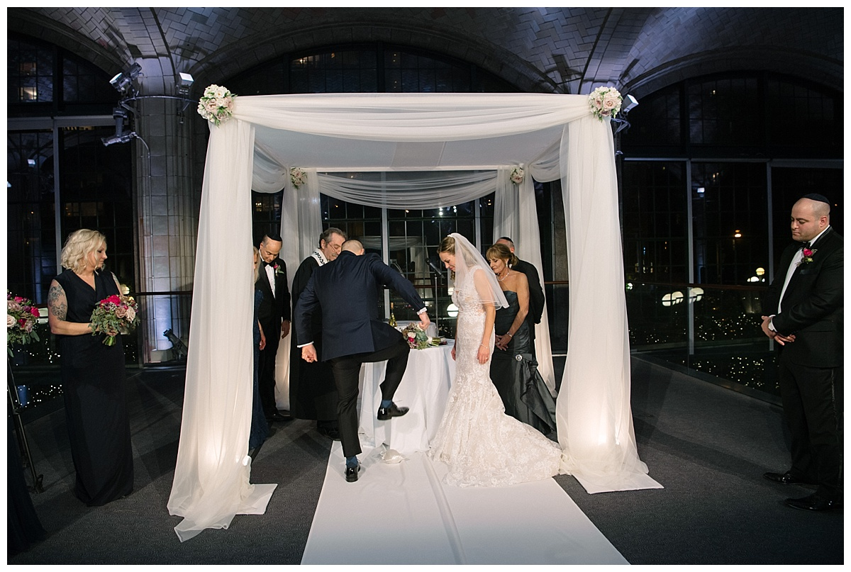 A groom stepping on a glass during a jewish wedding ceremony at Guastavinos in New York City. Dress by Ines Di Santo.