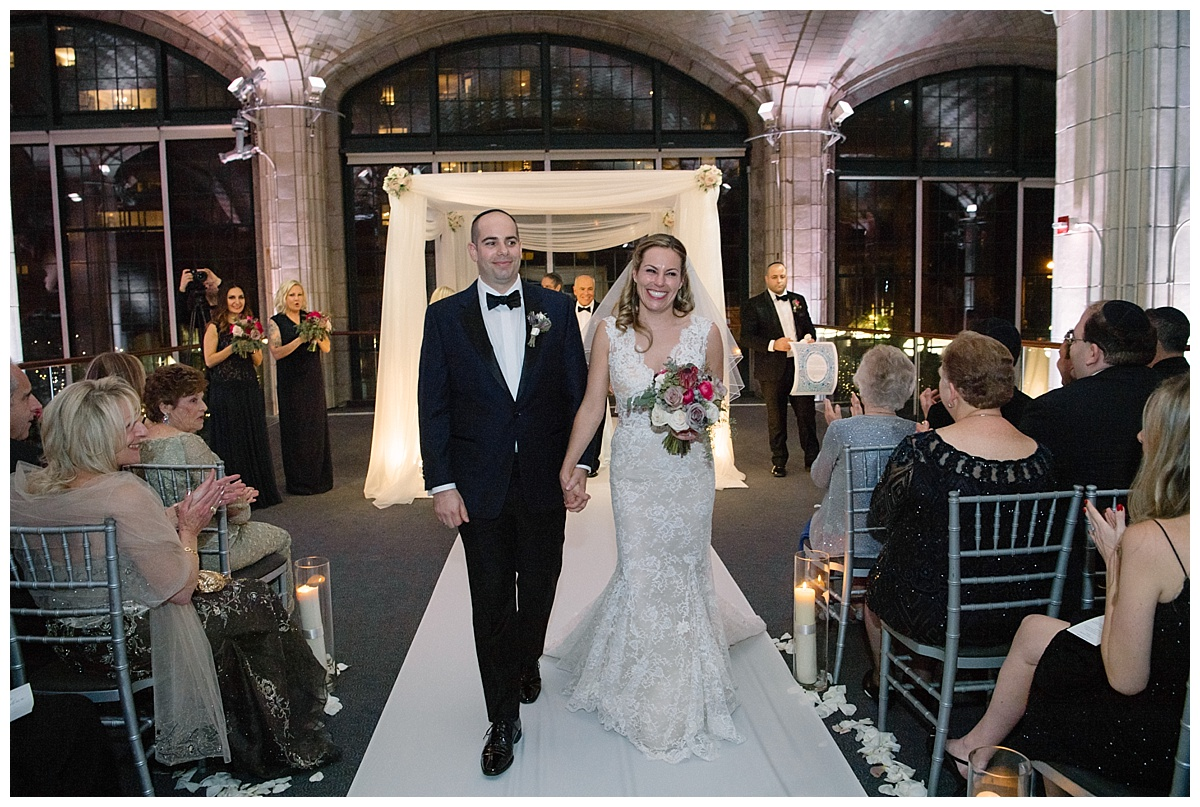 A newly wedded couple exiting their jewish wedding ceremony at Guastavinos in New York City. Dress by Ines Di Santo.