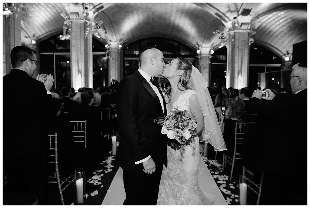 A newly wedded couple kissing while their exit from a jewish wedding ceremony at Guastavinos in New York City.